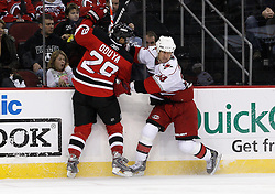 Oct 17, 2009; Newark, NJ, USA; Carolina Hurricanes right wing Scott Walker (24) hits New Jersey Devils defenseman Johnny Oduya (29) during the third period at the Prudential Center. The Devils defeated the Hurricanes 2-0.
