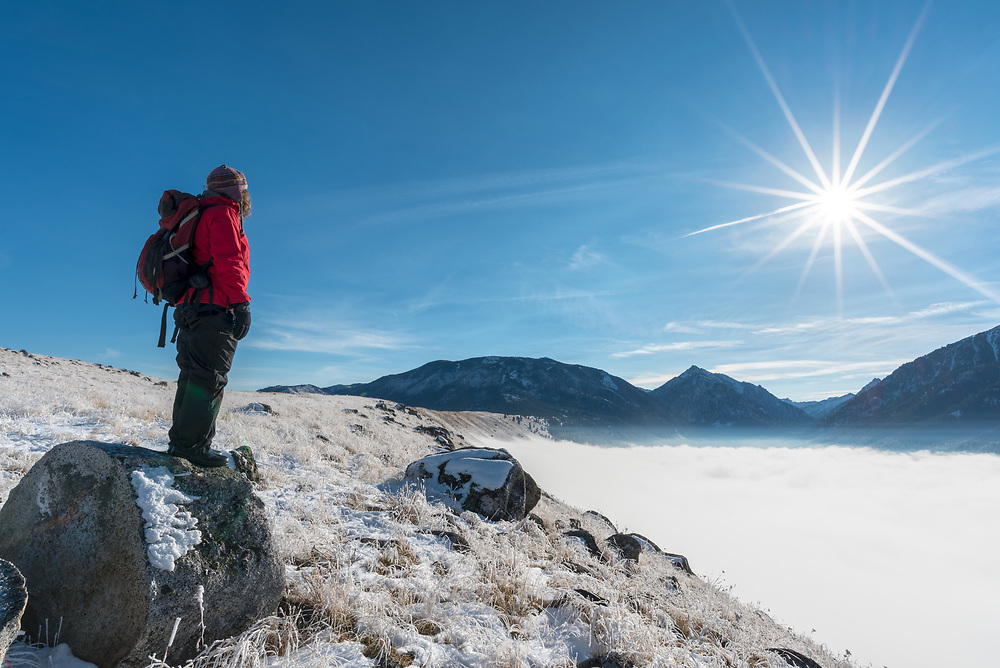 Hiker gazing on Wallowa Lake's east moraine gazing out at the Wallowa Mountains and fog filling the lake basin, Oregon.