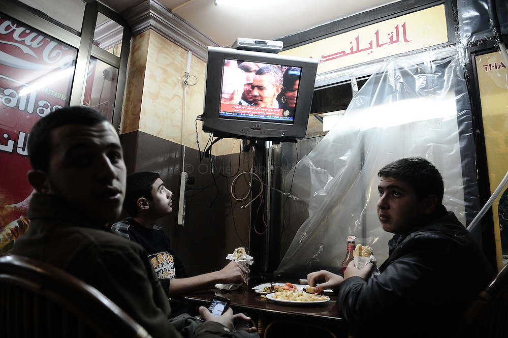 "Palestinian youths watch the live televised inauguration ceremony for US President Barack Obama at a restaurant in Gaza City on January 20, 2009. Barack Obama took the oath of office to become the first black president in US history today, proclaiming America had chosen ""hope over fear"" and must unite in a ""new era of responsibility"" to triumph over its multiple crises."