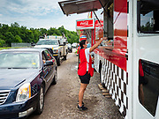 "26 JUNE 2020 - DES MOINES, IOWA: NADINE GARCIA, a worker at Fair Food Friday in Des Moines, hands a turkey leg to a customer. The 2020 Iowa State Fair, like many state fairs in the Midwest, has been cancelled this year because of the COVID-19 (Coronavirus) pandemic. The cancellation of the fair left many small vendors stranded with no income. Some of the fair food vendors in Iowa started ""Fair Food Fridays"" on a property a few miles south of the State Fairgrounds. People drive up and don't leave their cars while vendors bring them the usual midway fare; corndogs, fried tenderloin sandwiches, turkey legs, deep fried Oreos, lemonaide and smoothies. Fair Food Friday has been very successful. The vendors serve 450-500 people per Friday and during the lunch rush people wait in line in their cars 30 - 45 minutes to place an order.      PHOTO BY JACK KURTZ"