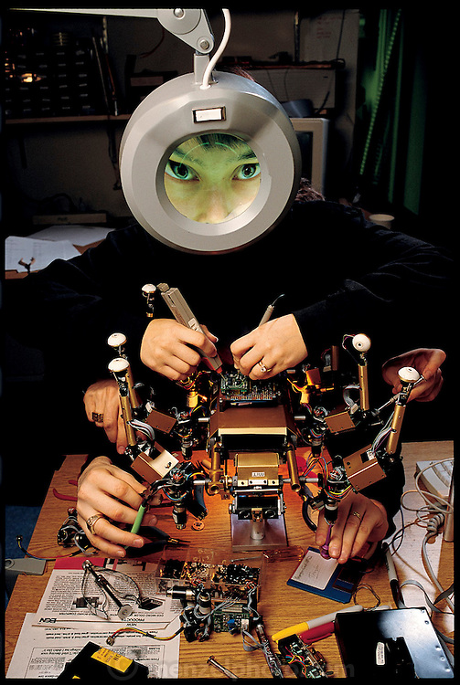 One of Rodney Brook's team's first subsumptive robots was the insectoid Attila (in photo from 1991), here being worked on by graduate student Cynthia Breazeal. The other pairs of hands belong to then-undergraduate student Mike Binnard, and former graduate student Colin Angle, who is now chief executive officer of the robotics firm iRobot. MIT Artificial Intelligence Lab, Cambridge, MA. From the book Robo sapiens: Evolution of a New Species, page 60.