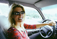 Portrait of smiling woman in drivers seat wearing sunglasses