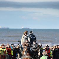 Nederland, Scheveningen , 23 november 2013.<br /> Generale repetitie aankomst van de Prins van Oranje op het Scheveningse strand .<br /> Zij bereiden zich voor op de feestelijke start van de&nbsp;viering van tweehonderd jaar koninkrijk, een week later. <br /> Op de foto: Koning Willem I (gespeeld door acteur Huub Stapel) wordt bij aankomst op het Scheveningse strand in de koets getild<br /> <br /> Anders dan in 1813 hebben alle betrokkenen ditmaal de kans om de landing vooraf te oefenen. Dat is maar goed ook want het programma voor 30 november is uitdagend en spectaculair. De meeste spelers en figuranten komen uit Scheveningen zelf en hebben geen toneelervaring. Regisseur Aus Greidanus begeleidt hen bij hun debuut. Hoofdrolspeler Huub Stapel moet op het juiste moment het strand op varen waarna hij overstapt op een originele &lsquo;nettenwagen' die door paarden wordt voortgetrokken. <br /> <br /> De&nbsp;aankomst van de latere koning Willem I wordt sinds 1813 iedere 25 jaar herdacht door de Scheveningse bevolking. Vanwege de viering van 200 jaar koninkrijk wordt dit keer extra groot uitgepakt. Dankzij de hulp van de Koninklijke Marine zijn op 30 november onder meer enkele grote marineschepen, sloepen en landingsvaartuigen aanwezig. Daarnaast speelt het Britse marineschip HMS Tyne een belangrijke rol bij het evenement. <br /> <br /> Dress rehearsal arrival of the Prince of Orange on the beach of Scheveningen (1813), in preparation for the start of the festive celebration of two hundred years kingdom, a week later.