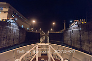 The Gatun locks in the Panama canal open to a ship at nighttime.