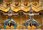 Guardian mythical demons or Yaksha  supporting the base of a golden Chedi at Wat Phra Kaew on the grounds of The Grand Palace; Bangkok, Thailand.