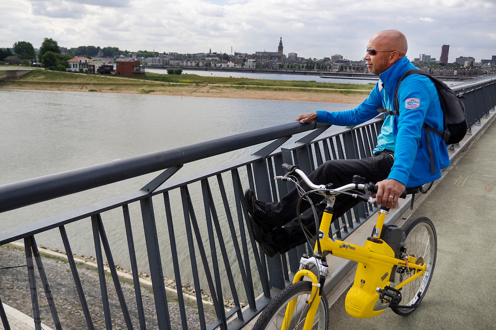 In Nijmegen kijkt een man op zijn elektrische fiets vanaf 'De Snelbinder', de fietsbrug tussen Nijmegen en Lent, over de Waal.<br /> <br /> In Nijmegen a man sits on his electric bike looking at the view of the river Waal.