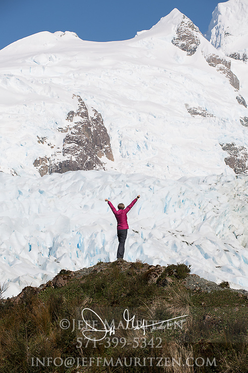 A woman hiker holds up her arms while viewing Bernal glacier (Benito glacier) located in Alacalufes National Reserve, Southern Chilean Fjords.