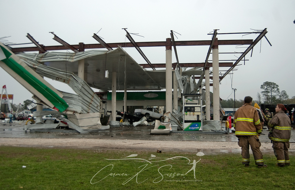 Mindy Bailey and Lisa Chestang of the Theodore-Tillman's Corner Volunteer Fire Department stand in front of a destroyed BP gas station following a tornado March 9, 2011 in Theodore, Ala. Three people were injured, and 17,000 residents were left without power following the storm. (Photo by Carmen K. Sisson/Cloudybright)