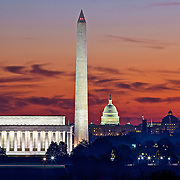 Dawn breaks with a pink orange sky over the Lincoln Memorial, Washington Monument and US Capitol building in Washington, DC