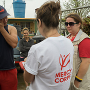 OCTOBER 18 - MARICAO, PUERTO RICO - <br /> Argenis Ramos, 34, wipes a tear as his wife Karian Batista, 30, stands in the background, while answering questions for  field research survey by Mercy Corps staffers Alexa Swift and Jill Monroe following the destructive path of hurricane Maria in Indiera Baja neighborhood.<br /> (Photo by Angel Valentin for NPR)