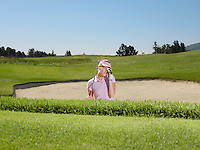 Young female golfer in sand trap looking through telescope