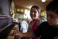 Yuliana Viloria sonrie mientras su hermano, Miguel Alejandro toca el piano de su abuelo. Gracias a FundaHigado, Yuliana recibió un trasplante de higado que le permite disfrutar de la vida. Punto Fijo, Venezuela 26 y 27 Oct. 2012. (Foto/ivan gonzalez)