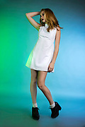 Fashion pose of Houston model Lauran Burke against blue and green gradient background.