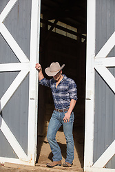handsome cowboy by a barn