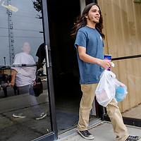 Family, Career & Community Leaders of America volunteer Marcus Sena carries groceries from  the First Baptist Church for a community member in Grants Thursday.