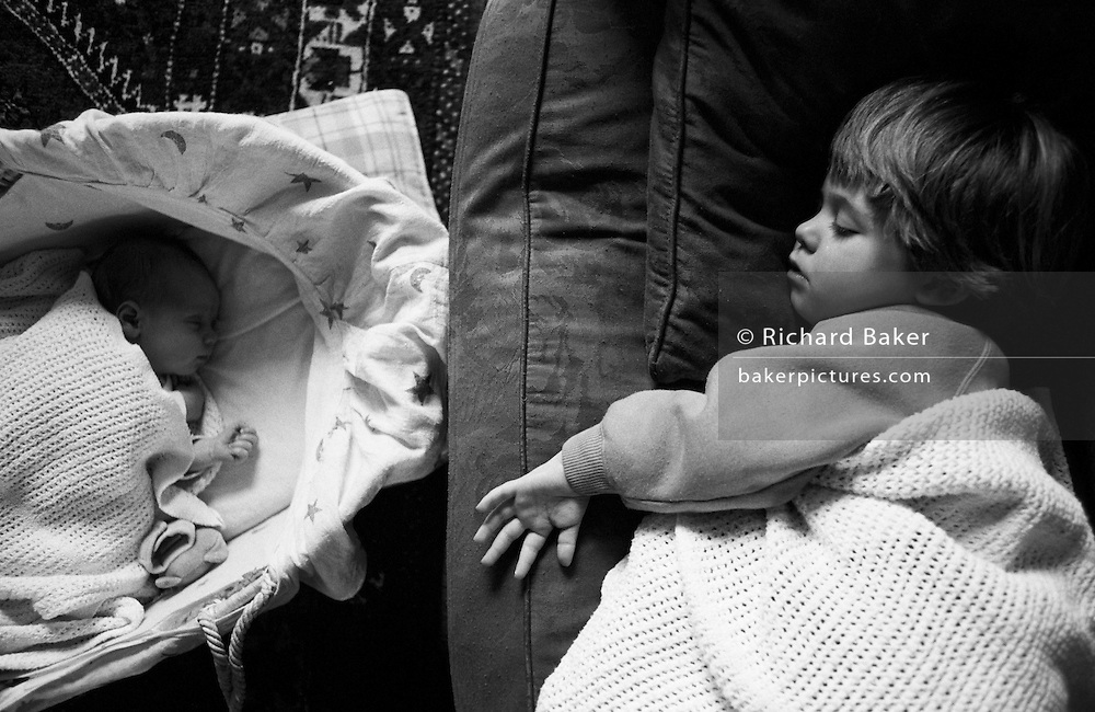 """A two and half year-old girl has a mid-afternoon sleep on the sofa of her parents' home in South London. On the floor is her young baby brother who is also enjoying some rest in his carrying basket. Both are unconscious but getting welcome shut-eye from the morning's activities. Both children face each other during deep sleep and we see the different sizes of their small hands. From a personal documentary project entitled """"Next of Kin"""" about the photographer's two children's early years spent in parallel universes. Model released."""