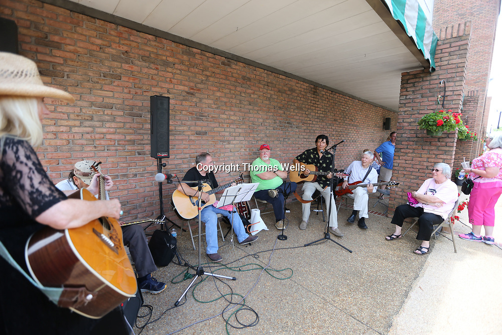 "Local Elvis tribute artist Jack Curtis sits in and plays with the ""Monday Night Pickers"" outside Reed's department Store Saturday afternoon before the gates opened at Fairpark for Saturday nights  Elvis Presley Festival."