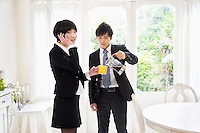Man pouring tea while woman talking on cell phone