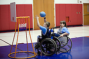 """Kellogg Foundation Assignment: Wheelchair Basketball..Conner Riffenhouse shoots the ball as Kaycee Stebleton plays defense...The contact is Pam Patula, 888/957-6245 runs an organization.called Socil (S.E. center for Independent Living )a member of April.  A weekly wheelchair basketball game in Lancaster, held on Jan 20th. Saturday at 10am. The basketball coach, Brett Harbage, is an Independent Living Specialist from SOCIL.  Other coach is Cheryl """"Hutch"""" Hutchinson, she is the adaptive physical education instructor of Fairfield County.  The adaptive basketball games are part of the Upward Basketball league, .  This is only Upwards adaptive league in the nation."""