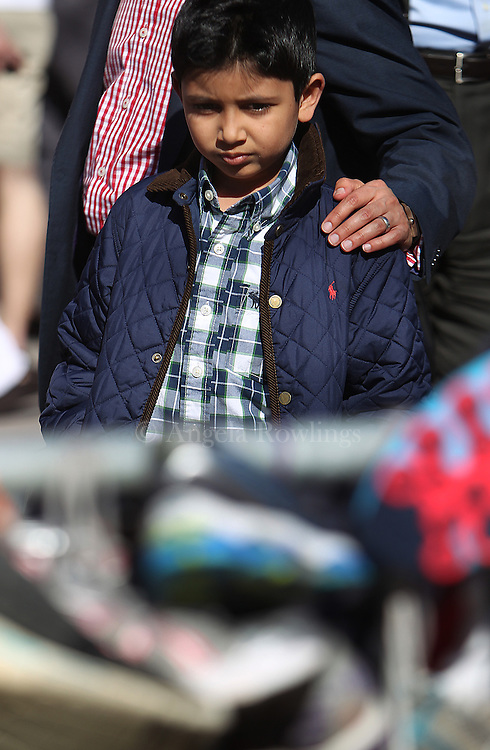 (Boston, MA - 4/25/13) Hitash Chawda of Needham rests his hand on the shoulder of his son, Shaylan Chawda, 7, as they pause at the memorial for Boston Marathon bombing victims in Copley Square, Thursday, April 25, 2013. Shaylan Chawda said he left his Captain America toy in honor of Martin Richard, 8, who was killed in the blasts. Staff photo by Angela Rowlings.