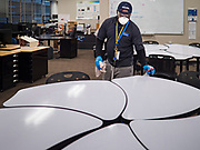 "19 MARCH 2020 - DES MOINES, IOWA:  SAM TEAH, a worker for the Des Moines Public Schools, cleans a computer arts classroom at Central Campus, a high school in the Des Moines Public Schools system. Des Moines schools are closed for at least 30 days because of the coronavirus and officials are using the time to ""deep clean"" and sanitize each school. On Thursday morning, 19 March, Iowa reported 38 confirmed cases of the Coronavirus. Restaurants, bars, movie theaters, places that draw crowds are closed for at least 30 days. There are no ""shelter in place"" orders in effect anywhere in Iowa but people are being encouraged to practice ""social distancing"" and many businesses are requiring or encouraging employees to telecommute.      PHOTO BY JACK KURTZ"