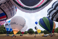 © Licensed to London News Pictures.  01/08/2018; Bristol, UK. Press preview event for the Bristol International Balloon Fiesta 2018 which will take place from 09 - 12 August. Balloons are inflated in the early morning light at Bristol's Ashton Court Estate, on the site of the first ever fiesta 40 years ago, and fly over the Clifton Suspension Bridge. Photo credit: Simon Chapman/LNP