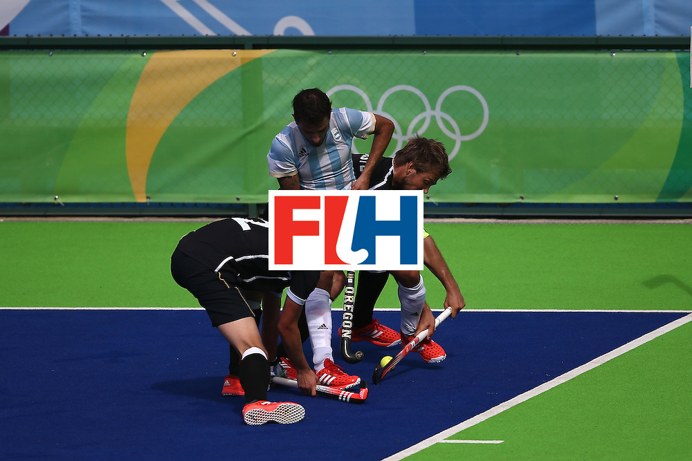RIO DE JANEIRO, BRAZIL - AUGUST 11:  Mathias Muller #2 and Moritz Furste #21 of Germany defend against Manuel Brunet #24 of Argentina during a Men's Preliminary Pool B match on Day 6 of the Rio 2016 Olympics at the Olympic Hockey Centre on August 11, 2016 in Rio de Janeiro, Brazil.  (Photo by Sean M. Haffey/Getty Images)