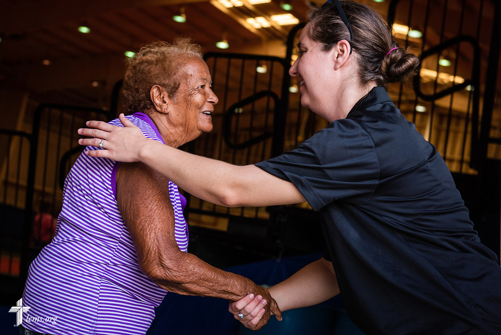 Teacher Ruth Maita from Casa de Amparo y Respuesta a Desastre (CARD), or House of Refuge and Mercy Response mercy center, gives a resident a hug during a food distribution event at a local community center on Tuesday, April 17, 2018 in Mayagüez, Puerto Rico. LCMS Communications/Erik M. Lunsford