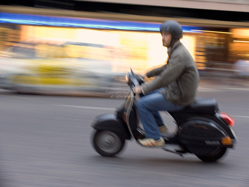 Man riding scooter at dusk in Piazza Garibaldi, Padua, Italy