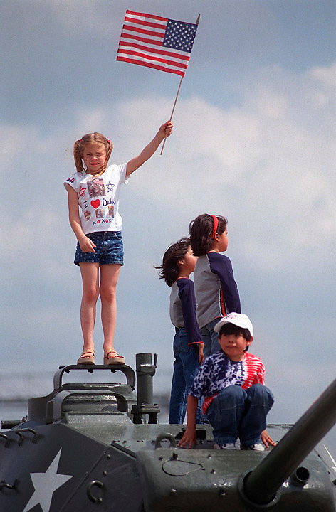 Abbi Bullock, 8, of Marion, waves a U.S. flag in the air as (front to back) Fabian Hammill, 5, and his two sisters Jessina, 8, and Emaya, 7, all of Cedar Rapids, look on after the Iowa National Guard's 234 Signal Battalion homecoming ceremony at Veterans Memorial Stadium Saturday, May 8, 2004 in Cedar Rapids. The unit was activated and stationed in Iraq March 15, 2003.