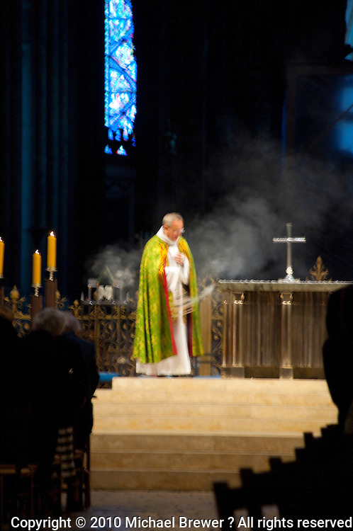 Our Lady of Chartres Cathedral, Chartres, France. Priest swinging a smoking censer in front of the altar.