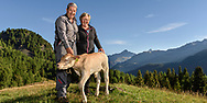 Erna and Bruno Salis with a calf on the Alp Motta above Bivio on a nice and sunny summer morning in August with the Piz Mitgel in the background, Parc Ela, Grisons, Switzeland