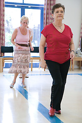 Older women taking part in a line dancing activity,