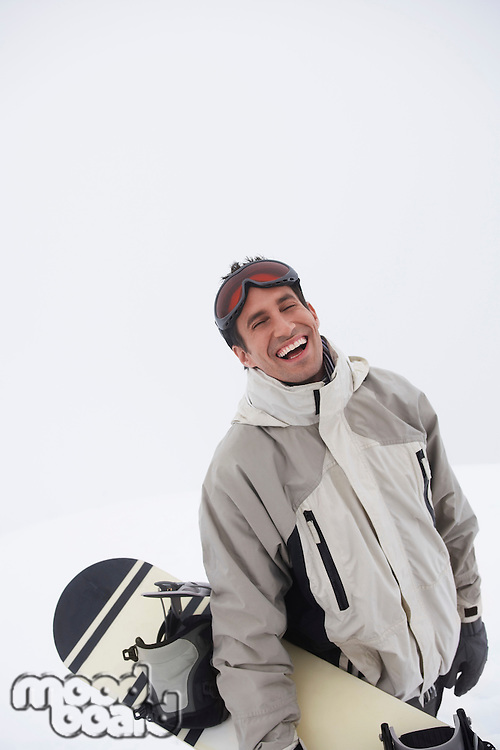 Man standing on snow carrying snowboard portrait