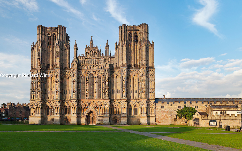 View of Wells Cathedral from the Cathedral Green in the late evening, lit by the sun.