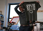 "Democratic 2020 presidential candidate Beto O'Rourke, 46, holds up a ""Iowa For Beto"" screen-printed shirt at Raygun clothing store during a three day road trip across Iowa, in Cedar Rapids, Iowa, U.S., March 15, 2019.  REUTERS/Ben Brewer"