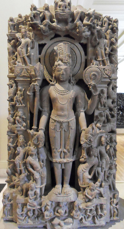 Sandstone stele with a figure of Harihara From Khajuraho, Madhya Pradesh, central India, 10th century AD. The composite form of Shiva and Vishnu. By the sixth century AD the sects of both Shiva and Vishnu were well developed. icons such as this synthesised the two deities. Sculptures like this one would have been fitted into a niche in a temple wall. The main four-armed standing figure is divided vertically through the centre, its proper right side (that is, on the left of this picture) being Shiva and the left, Vishnu.The matted locks of Shiva's hair are built up in an elaborate coif and adorned with a serpent and skull. He holds a rosary and a trident symbolic of his ascetic nature and his power. Shiva's third eye has been carefully incised on Shiva's side of the face. The left side of the image balances these attributes perfectly for Vishnu.