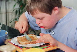 Teenage boy with Downs Syndrome sitting at breakfast table spreading marmalade onto slice of toast,