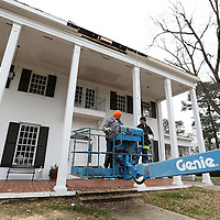 Adam Robison | BUY AT PHOTOS.DJOURNAL.COM<br /> Dewayne Grimes and Johnny Griffin, with Grimes Construction in Mooreville, ride their lift up to the roofline at the Old Rogers Home that is now Fleur De Lis Antiques to replace rotted fascia boards Tuesday afternoon in Tupelo.