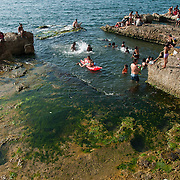 Residents of Havana, Cuba, swim and socialize on the rocks, and in the Banos del Mar, or sea baths located just below the Malecon, or seafront wall and walkway, bordering the edge of the city.  The sea baths, which are exposed at low tide, were cut out of the reef decades before the construction of the Malecon began in 1901. The baths are about 12 feet square and 6-8 feet deep, with rock steps for access and gaps to allow waves to wash in and out. The baths were originally designated before the turn of the century with separate areas for men, women, and negros. Photo by Jen Klewitz