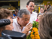 16 JANUARY 2013 - BANGKOK, THAILAND: SUKHUMBHAND PARIBATRA, candidate for Governor of Bangkok, talks to a Thai voter who handed him a flower garland during a campaign appearance on Silom Road in Bangkok. The Oxford educated Sukhumbhand is a member of the Thai royal family (he is a great grandson of the late Thai King Chulalongkorn). He is a member of the Thai Democrat party and was first elected Governor of Bangkok in 2009. He is running for reelection this year. Sukhumbhand faces six challengers in the March 3 election. His toughest opponent is expected to be Police General Pongsapat Pongcharoen, who is running under the banner of the Pheu Thai Party, which controls the Prime Minister's office and Parliament.     PHOTO BY JACK KURTZ