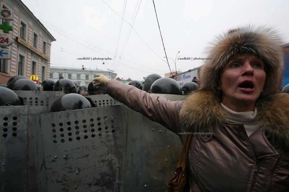 Eine Demonstantin empoert sich ueber die Sicherheitskrate der OMON, die mit Schlagstoecken und Schilden gegen die Demonstranten vorgeht. Nachdem rund 2000 Menschen in Moskau eine Kundgebung gegen den russischen Praesidenten Putin abhielten, durchbrachen hunderte Oppositionelle Polizeisperren, um zur Zentralen Wahlkommision vorzudringen. Kraefte der Sondereinheit OMON stoppte den Protest und verhaftete mehrere Demonstranten. Auch der ehemalige Schachweltmeister und populaere Oppositionelle Garry Kasparow wurde inhaftiert. A female protester in front of a police line. After an opposition gathering in Moscow several thousand protesters tried to march on the Central Election Commission. After they broke police lines russian police broke up the march and detained serveral protesters, also the protest leader, former chess champion Garry Kasparov.