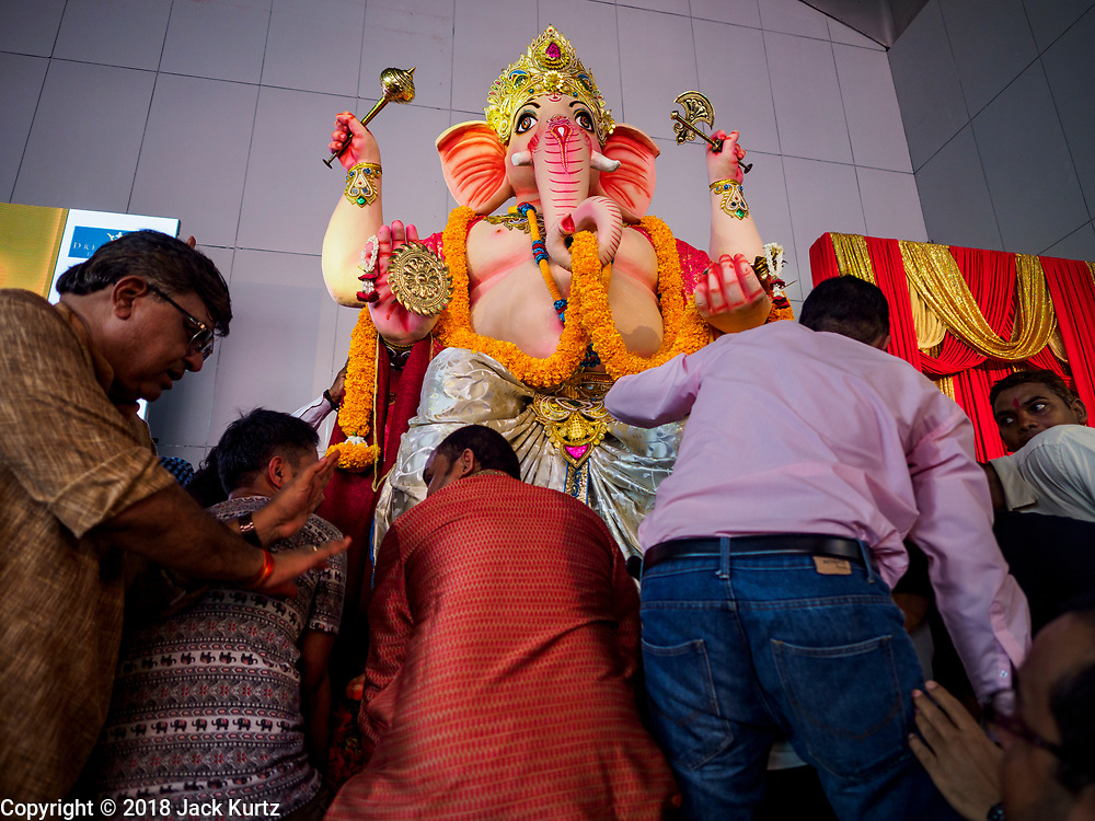 """23 SEPTEMBER 2018 - BANGKOK, THAILAND: Men move the Ganesha deity to a waiting truck at the Ganesha Festival at Wat Dan in Bangkok. The deity was put on a truck for a procession through Bangkok.  Ganesha Chaturthi also known as Vinayaka Chaturthi, is the Hindu festival celebrated on the day of the re-birth of Lord Ganesha, the son of Shiva and Parvati. The festival, also known as Ganeshotsav (""""festival of Ganesha"""") is observed in the Hindu calendar month of Bhaadrapada, starting on the the fourth day of the waxing moon. The festival lasts for 10 days, ending on the fourteenth day of the waxing moon. Outside India, it is celebrated widely in Nepal and by Hindus in the United States, Canada, Mauritius, Singapore, Thailand, Cambodia, and Burma.   PHOTO BY JACK KURTZ"""