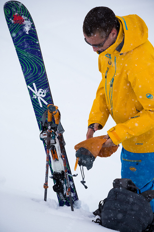 Tyler Hatcher pulls skins for another run in the Cascade backcountry during a spring storm.