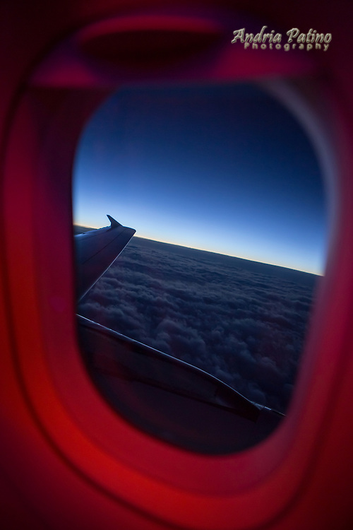 Dawn above the clouds from inside Plane Window