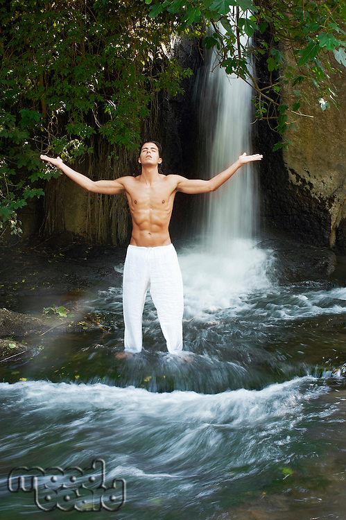 Man standing in river by waterfall meditating front view full length