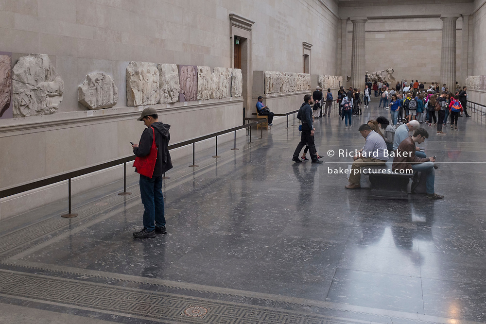 Visitors admire the Parthenon (Elgin) Marbles in Room 18 of the British Museum, on 12th June 2018, in London, England.