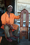 Africa. Kenya. Lamu Town..Carpenter with carved chair..CD0012