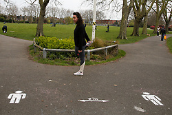 © Licensed to London News Pictures. 01/04/2020. London, UK. A woman exercising near social distancing marks on the pathway at a north London park as coronavirus lockdown continues. Photo credit: Dinendra Haria/LNP