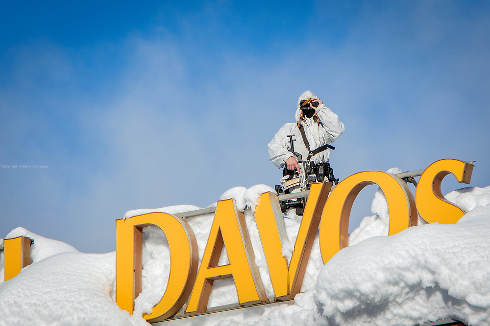 A police sniper surveys the area surrounding the World Economic Forum from a snipers nest on top of Hotel Davos.